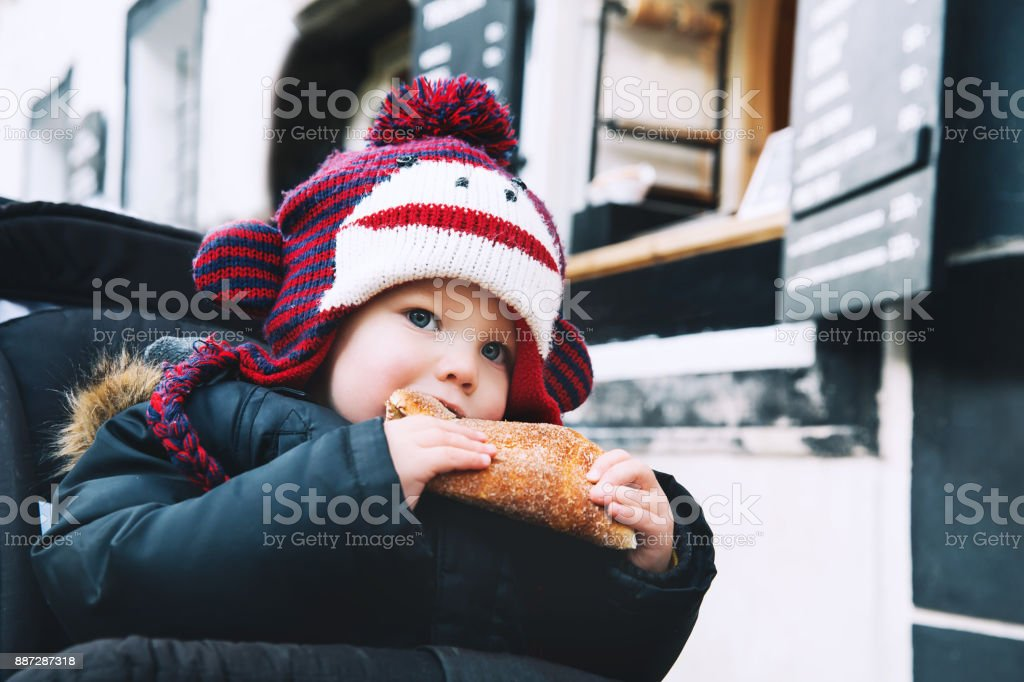 Child boy eating appetizing warm fresh Trdlo or Trdelnik with chocolate - Traditional National Czech Sweet Pastry Dough. stock photo