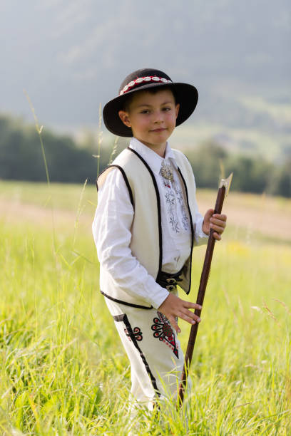 Child boy in traditional goral dress, hat and axe stands on meadow in Polish mountains stock photo