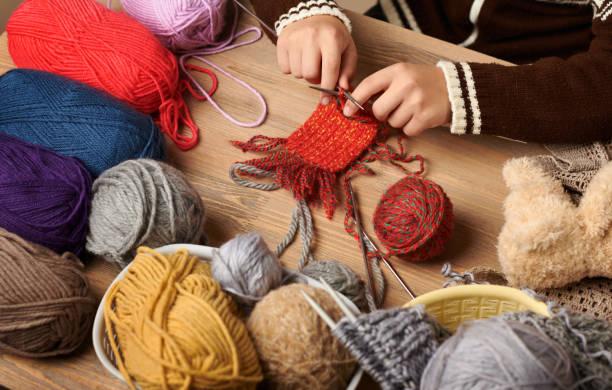 Niño niño es aprender a tejer. Hilados de lana de colores están en la mesa de madera. Acercamiento de la mano. - foto de stock
