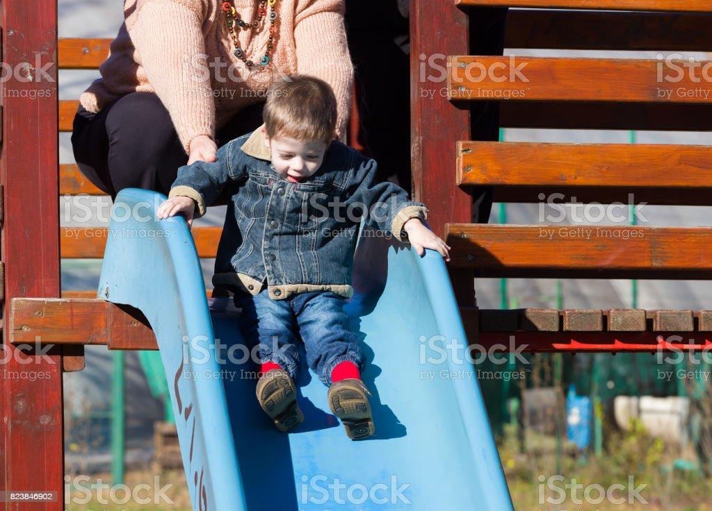 child boy on a slide in a park in autumn stock photo