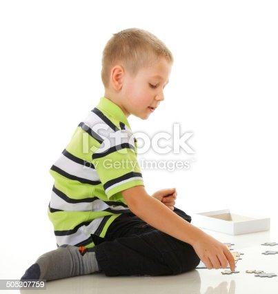 514261930 istock photo child boy playing puzzle isolated 505307759