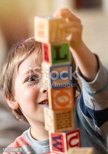 istock Child boy playing with alphabet blocks 1211220873