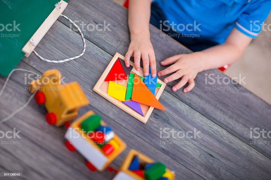 Child boy playing with toys at table stock photo