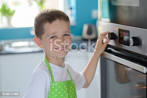 istock Child boy regulating temperature of the oven. 916072468