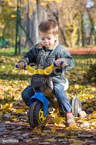 istock child boy ride a toy motorcycle in a park in autumn 840259044