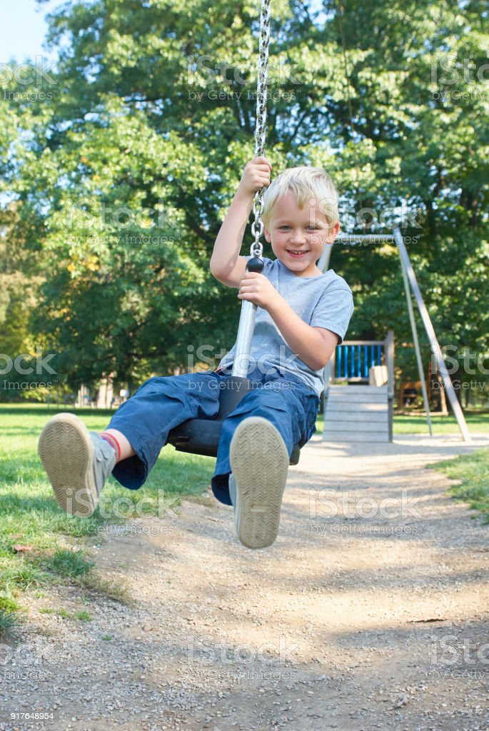 Child boy rides on Flying Fox play equipment stock photo