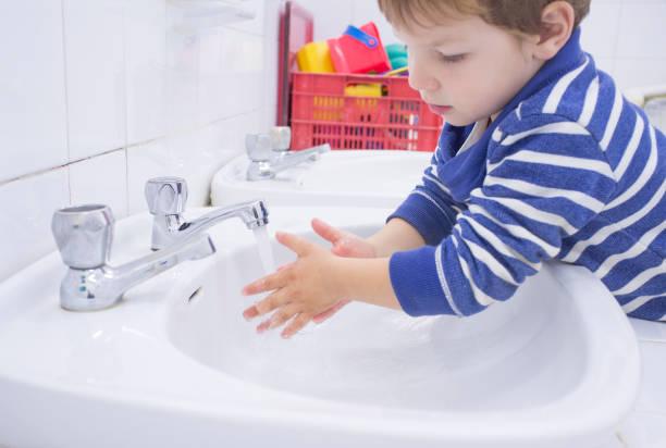 Niño niño lavando las manos en el fregadero escolar adaptado - foto de stock