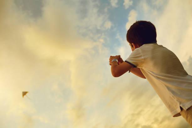 Kind Junge mit einem Drachen in den Himmel mit Wolken – Foto
