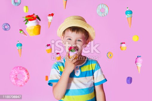 child boy with happy birthday cupcake on pink background with the flying sweets. Kid have a birthday party.