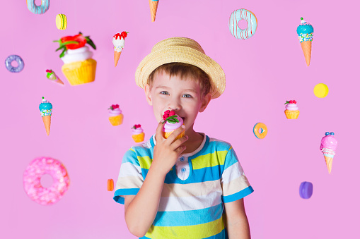 istock child boy with happy birthday cupcake on pink background with the flying sweets. Kid have a birthday party. 1155706947