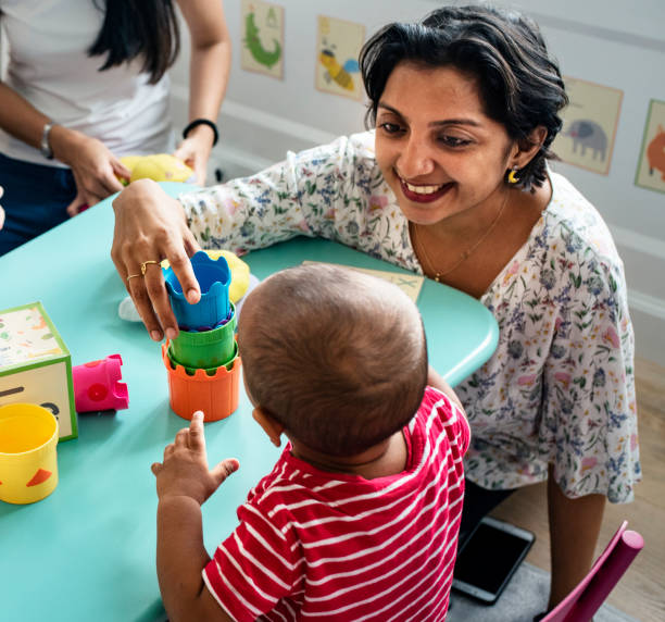 Child building blocks with a teacher in the nursery Child building blocks with a teacher in the nursery preschool teacher stock pictures, royalty-free photos & images