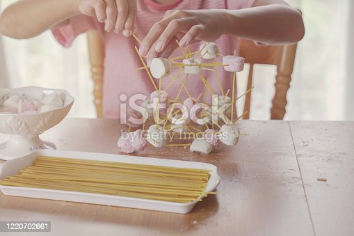 child building tower with spaghetti and marshmallow learning remotely at home, STEM science, homeschooling education, Social distancing, isolation concept