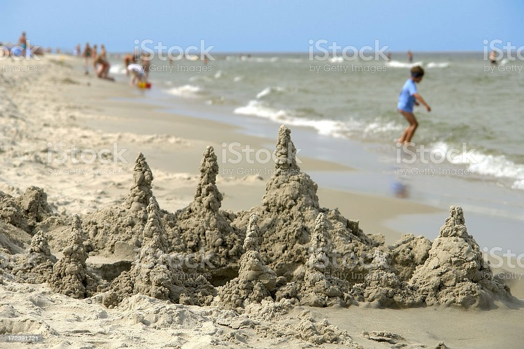 Child builds a sand castle on the beach, seaside royalty-free stock photo