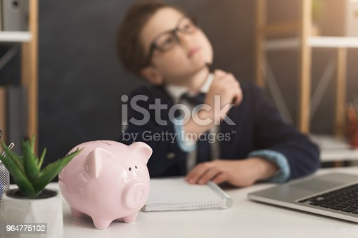 Pensive little businessman thinking of income at office table with piggy bank, selective focus