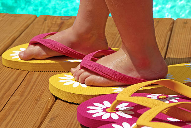 child by pool wearing flipflops stock photo