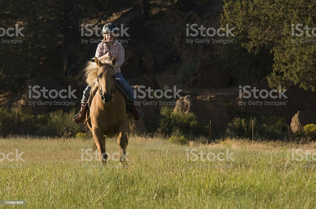 Child cantering on palomino stock photo