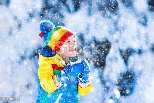 istock Child catching snow in winter park 620704290