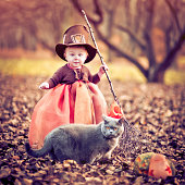 Little girl dressed as witch and her cat at Halloween