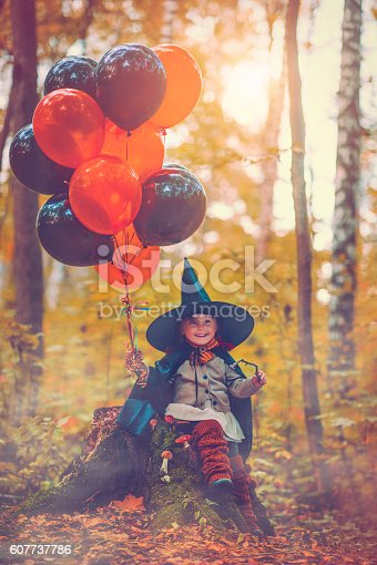 Little girl holding balloons and dressed as witch at Halloween