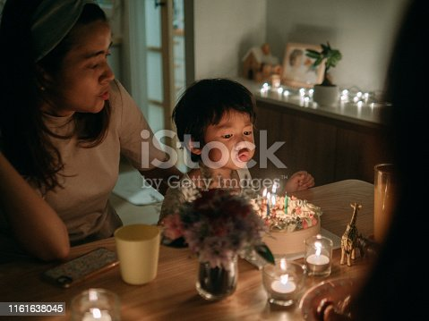 Happy asian family with cake and candles celebrating birthday at a party at home.