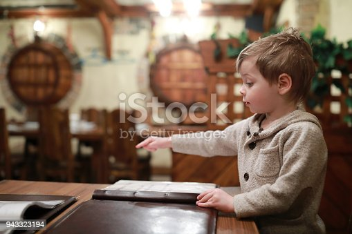 Child choosing dishes at table in restaurant