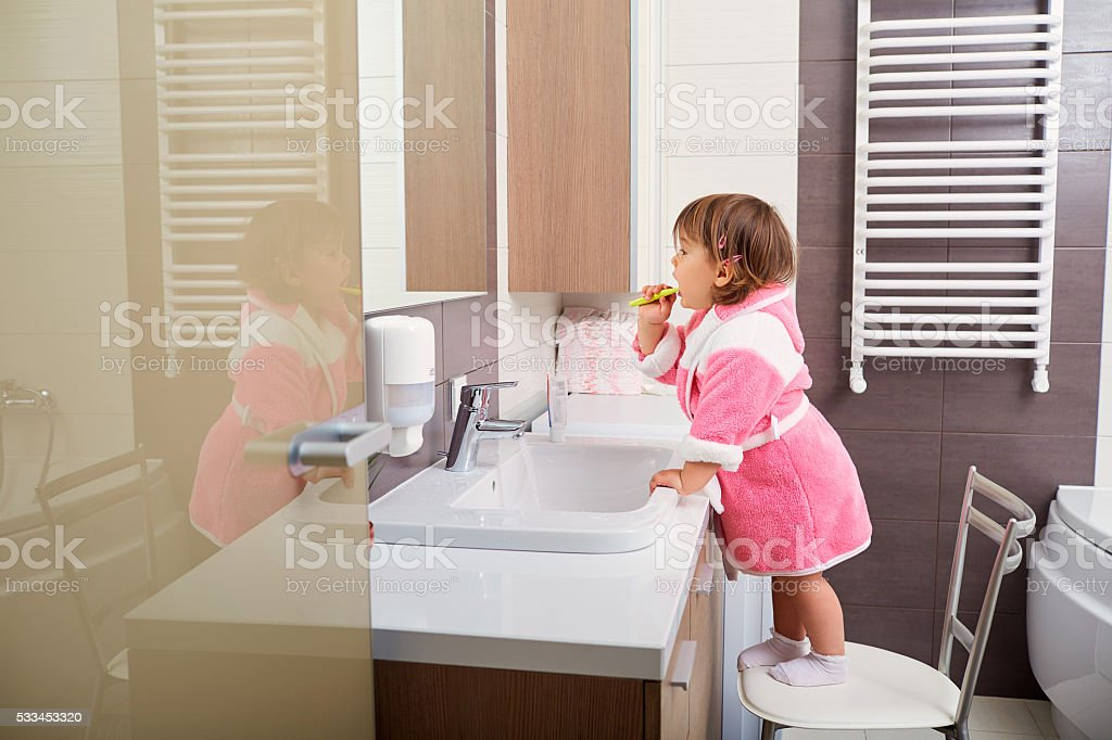 Child cleaning teeth in bathroom. stock photo