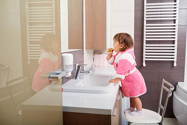 Criança limpeza dentes no banheiro. - foto de acervo