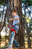child climbing in Adventure park in woods,outdoor