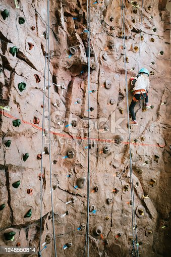 A Caucasian girl climbs a large bouldering  wall at a rock climbing gym.  A fun and healthy way to stay active and physically fit.  Shot in Washington state, USA.
