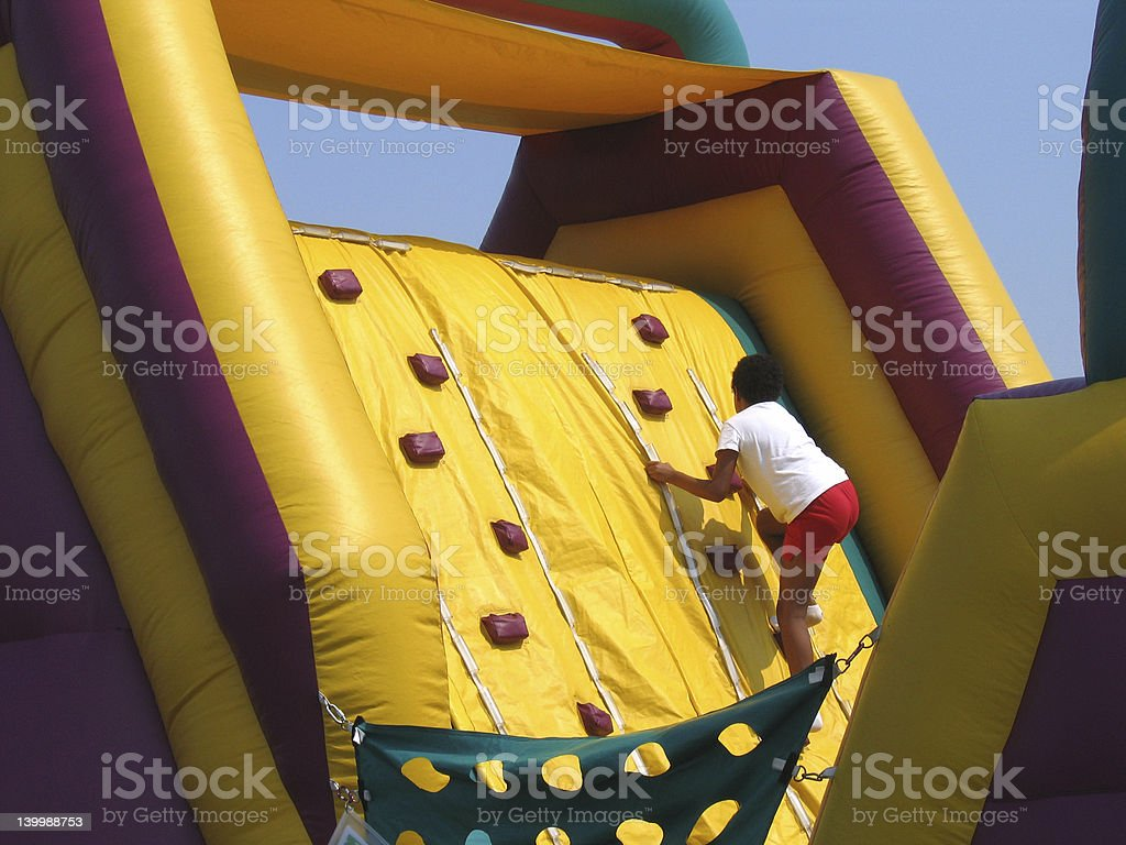 Child climbing up an inflatable climbing wall stock photo