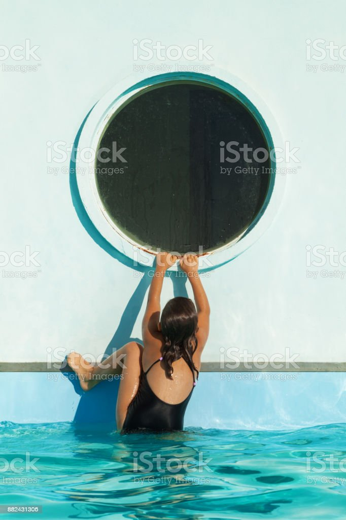 child climbs on the edge of the pool stock photo