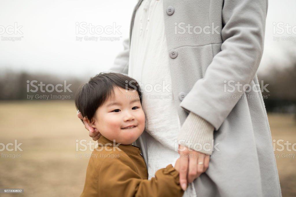 彼の妊娠中の母親の腹にしがみついている子供 ロイヤリティフリーストックフォト