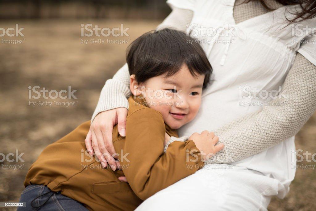 妊娠中の母親の腹にしがみついている子供 ストックフォト