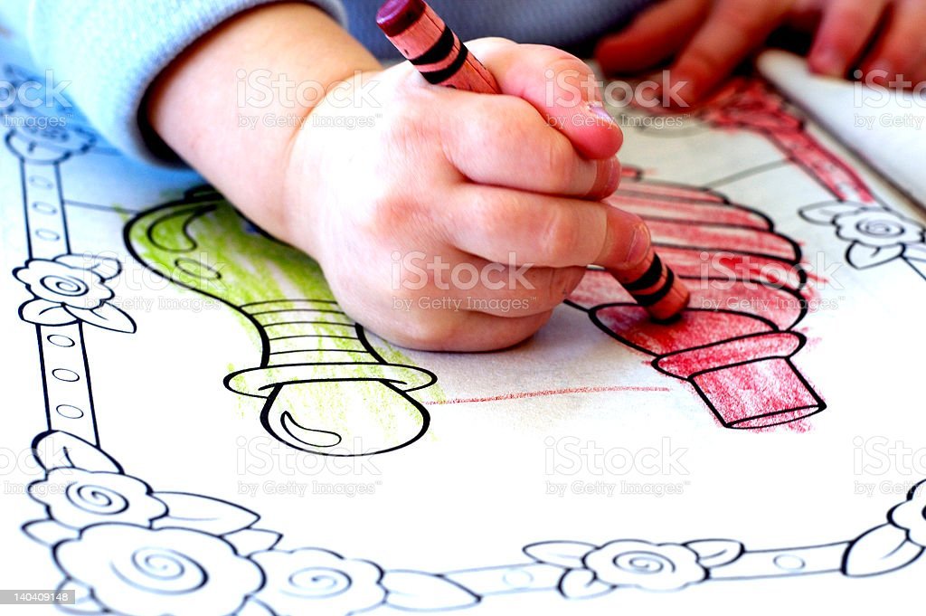 A child coloring in an activity book stock photo