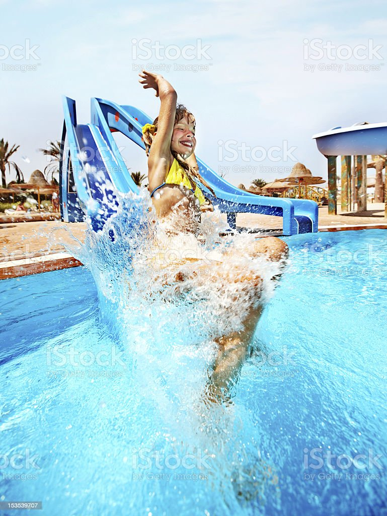 Child coming off of a water slide at an aqua park stock photo