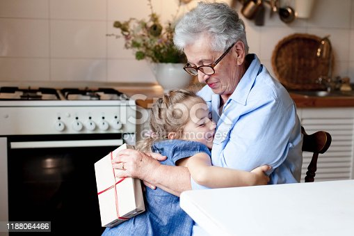 494086690istockphoto Child congratulates grandmother with gift box. Kid and senior woman are hugging 1188064466