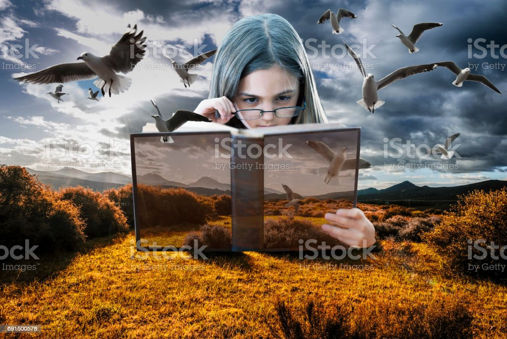 Child conjuring images from reading a book stock photo