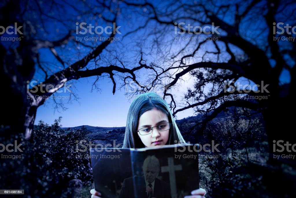 Child conjuring images from reading a spooky book stock photo
