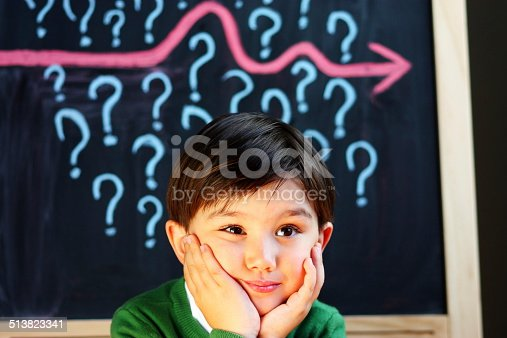 istock Child contemplating question marks 513823341