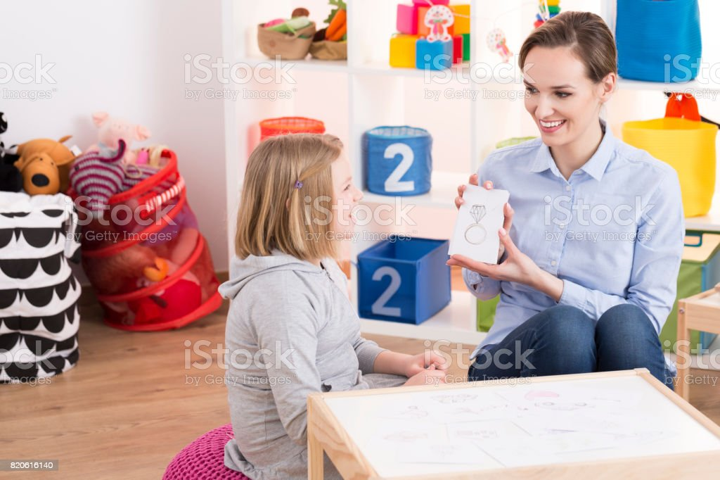 Child counselor and ADHD girl stock photo