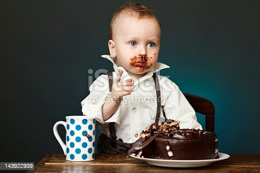 A Child Covered In Chocolate Cake On His Face Stock Photo