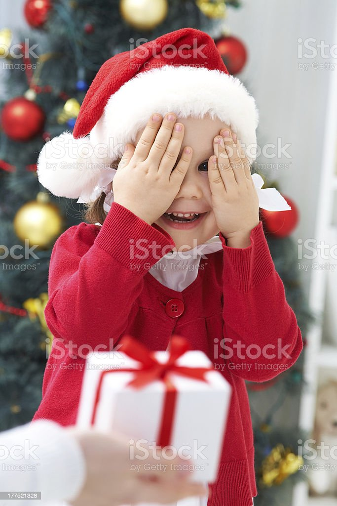 Child covering her eyes as she receives a Christmas present stock photo