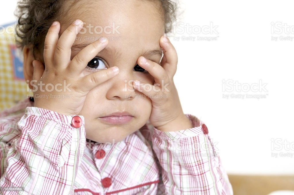 Child covering her head with hands against white background royalty-free stock photo