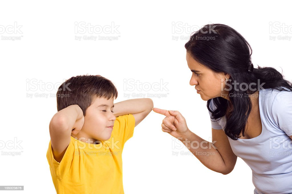 A child covering his ears from being scolded by his mother stock photo