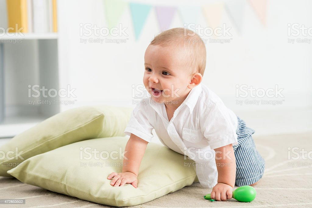 Child crawling on floor with toy in hand stock photo