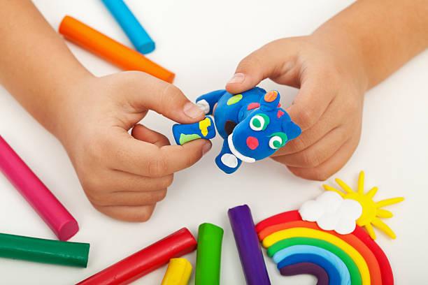 dziecko bawiąc się kolorowe gliny-zbliżenie na ręce - glina zdjęcia i obrazy z banku zdjęć