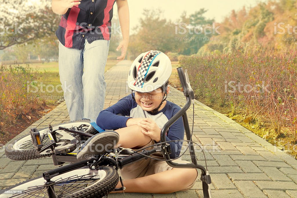 Child crying after falling from bicycle stock photo