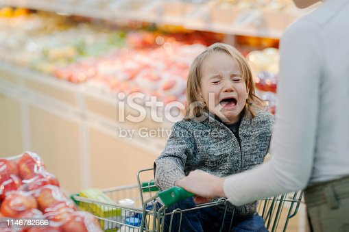 Young boy child crying temper tantrum in shopping cart with mother parent in produce section aisle of supermarket growing pains