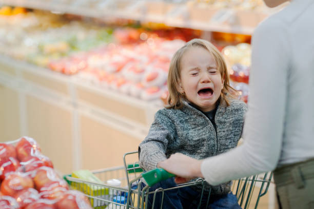 Child crying in shopping cart in supermarket stock photo