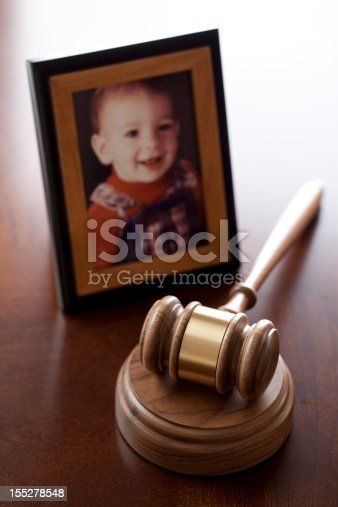 Concept for child custody showing gavel, and portrait of young boy.
